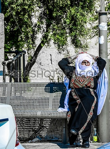 An Arab woman in traditional dress sits waiting for the bus in Jerusalem.