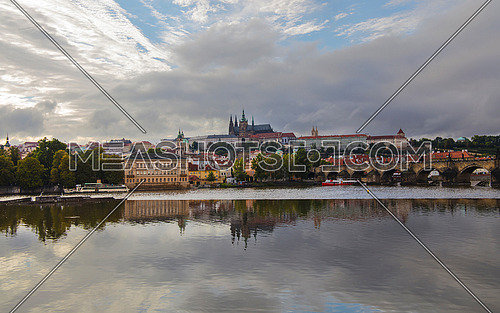 High angle panorama view of Prague old town, Charles Bridge, Royal castle and Saint Vitus Cathedral over Vltava river and cloudy sky sunny day
