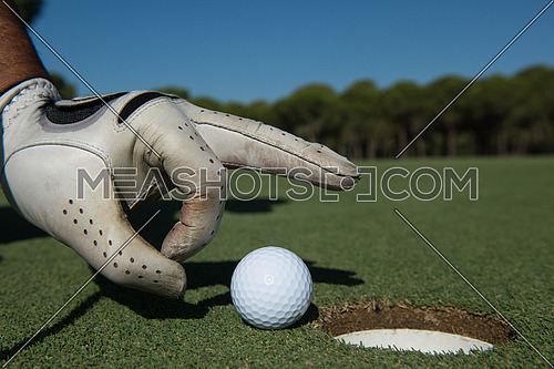 close up of man's hand putting golf ball in hole at course