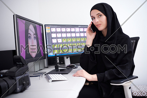Muslim female graphic designer talking on the phone. Freelancer editing photos on two monitors. Hijab girl on the work place