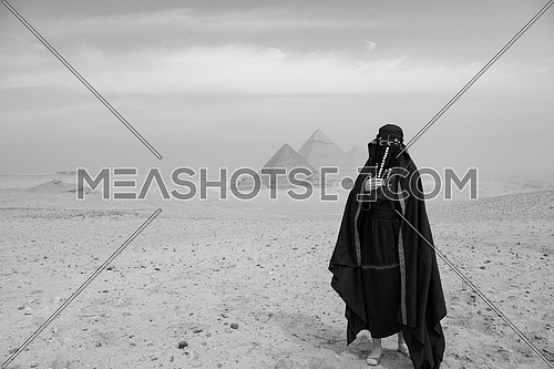 black and white shot of egyptian woman in traditional bedouin clothes in front of ancient giza pyramids