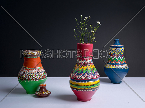 Studio shot of still life of three orange decorated pottery vases with small flowers in a background of white table and black wall with harsh shadow