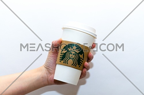 A female holding The traditional paper cup Starbucks coffee cup on a white background. December 2018 in Cairo, Egypt.