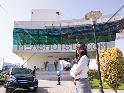 young business woman making phone call in front of corporate business building