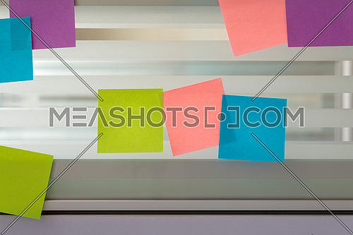 Three colored sticky notes surrounded by randomly scattered sticky notes over glass screen of a bench desk