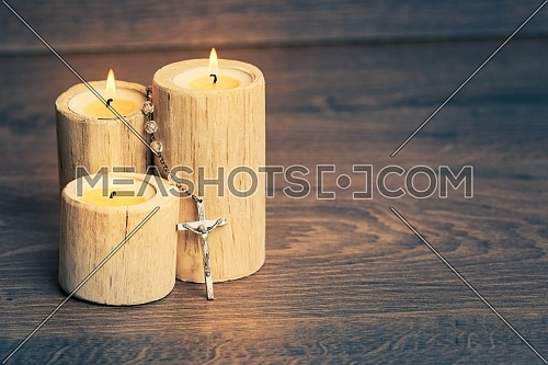 Silver rosary with Jesus on the Candle at wooden table,religion concept,vintage style with split toning.