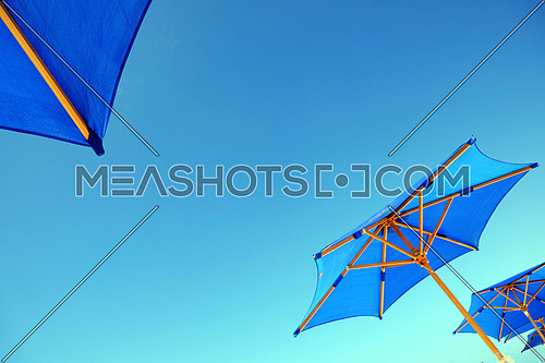 Blue Umbrellas against blue sky from low point of view