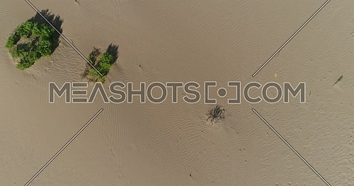 drone point of view landing in the desert showing sand and shrugs