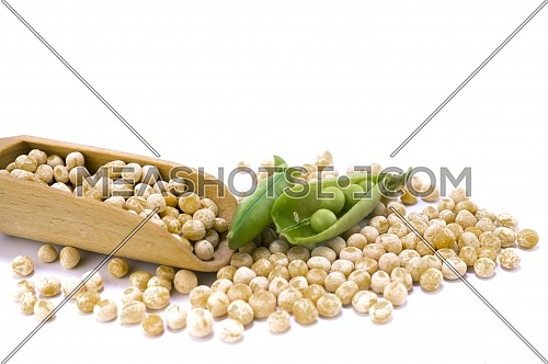 Dried peas spilling from a wooden scoop fresh plant with pods isolated on a white background