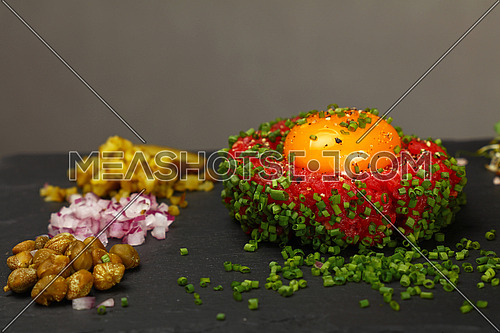 One portion of raw minced beef meat tartare steak with egg yolk, green chive, onions, cucumbers and capers on black slate board, close up, high angle view, personal perspective