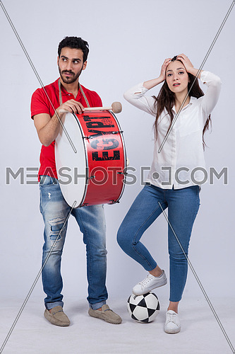 A young man holding big drums and a young woman cheering on a white background