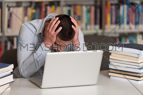 Stressed Student Of High School Sitting At The Library Desk - Shallow Depth Of Field