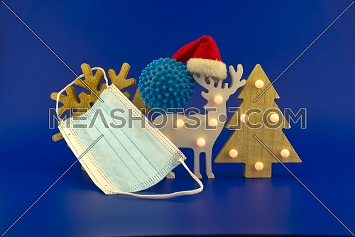 Christmas in pandemic concept still life with blue virus molecule, red Santa hat, Christmas tree, gift box and surgical face mask all isolated on blue background