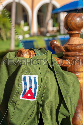 Green military hat with printed Cuban flag hanging in the sun, symbol of the Cuban revolution.