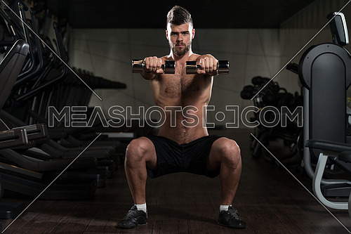 Young Man Performing Dumbbell Squats - One Of The Best Bodybuilding Exercise For Legs