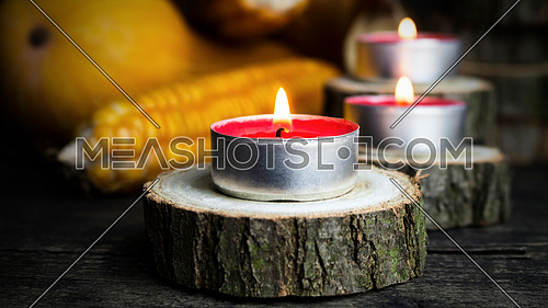 Burning Candles With Pumpkins, Corncob, autumn leaves in the background. Thanksgiving Day, Decoration on a wooden table