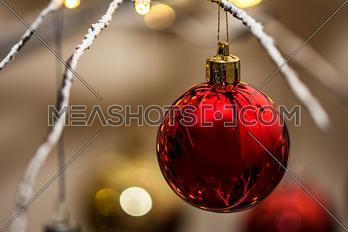 Close up of a red bauble hanging from contemporary christmas tree. Landscape orientation.