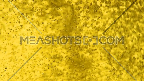 Close up background of pouring soda water with bubbles, sparkling wine, champagne or beer in glass, low angle side view, slow motion