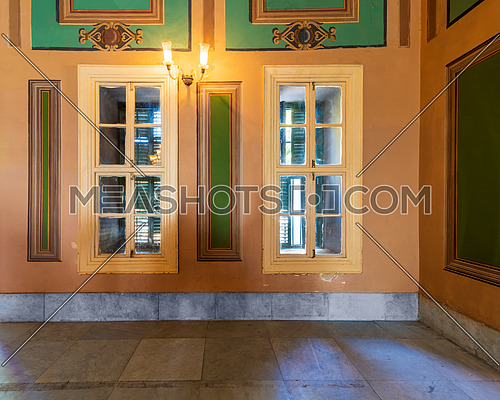 Corner orange wall with two narrow wooden window with closed green shutters, beautiful elegant rectangular green frames, and white tiled marble floor