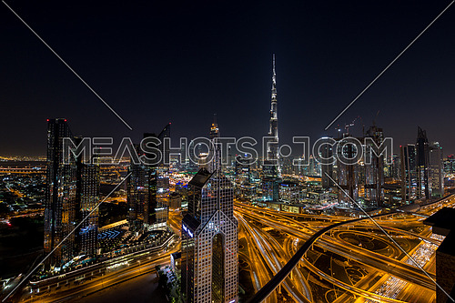 Extreme long shot for Dubai City showing Burj Khalifa and skyscrapers and traffic at night