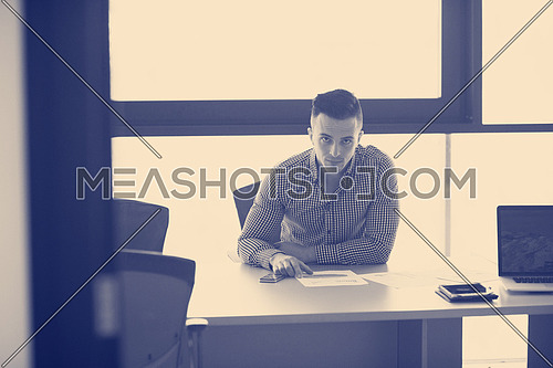 happy young businessman at his desk at work in modern startup business office interior