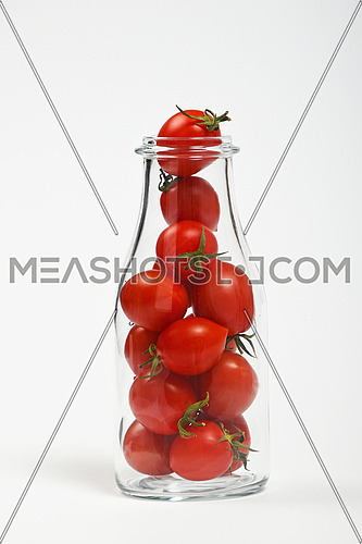 Big glass bottle full of cherry tomatoes over white background as symbol of fresh natural organic juice or ketchup