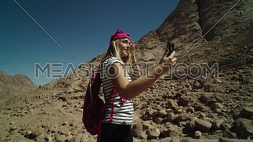 Track In shot for a female tourist wearing a pink cap and travel backpack taking a selfie at Sinai Mountain for wadi Freij at day.