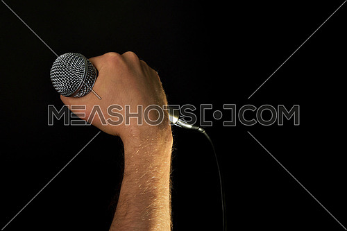 Male hand holding microphone with wire cable isolated on black background