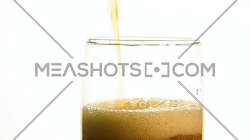 Close up of pouring carbonated cola soft drink in transparent glass until full over white background, low angle side view, slow motion