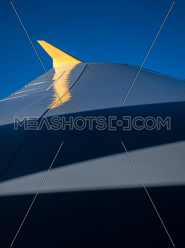 Plane wing during flight with blue skyes