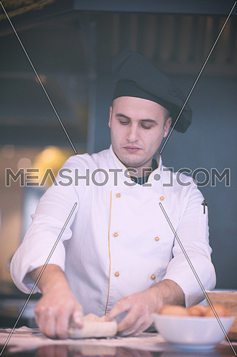 chef  preparing dough for pizza on table sprinkled with flour