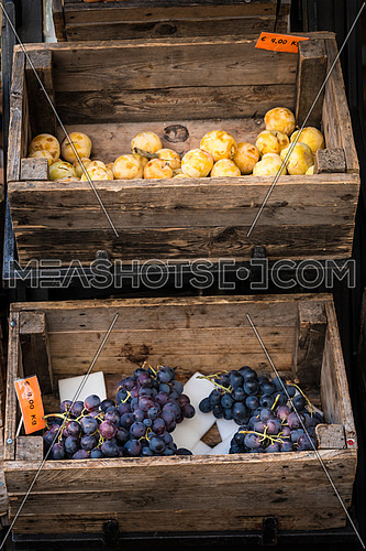 In the photo two old wooden boxes with inside the fruit (grapes and plums)