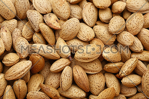 Whole raw almond nuts with brown nutshells on retail market, close up, background, high angle, elevated top view