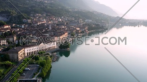 Drone view of Lake Iseo at sunrise, on the left the city of Lovere which runs along the lake,Bergamo Italy.
