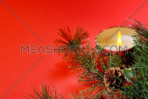 New year christmas tree fir branch, burning candle, decorations, on red background