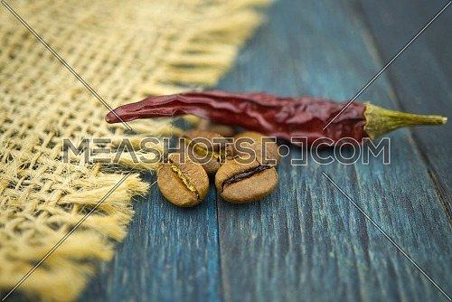 Macro photo of dried red chili pepper and roasted coffee beans on wooden and hessian or burlap fabric background