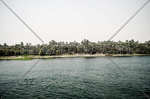 Long shot for the river Nile surrounding land, trees and plants at day
