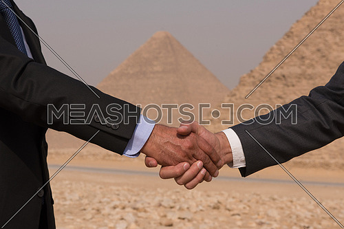 successful arab business people shaking hands over a deal with Egyptian giza pyramids in backgronud