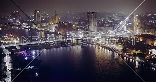 Aerial Shot from drone flying backward over the River Nile showing Bridge, Hilton Hotel and Television Network Building in cairo at night