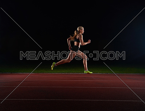 Athletic woman running onrace  track