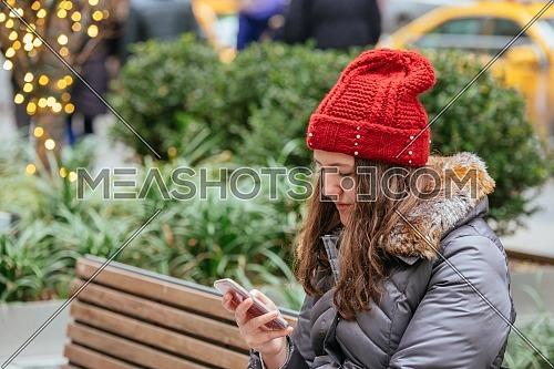 Young pretty girl using mobile phone in the street, light background