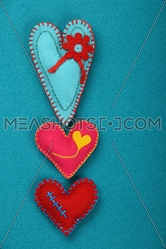 Felt craft and art, three handmade stitched toy hearts, pink, red and teal on blue felt background