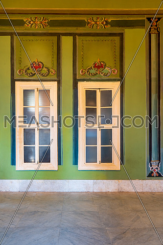 Two narrow closed windows and beautiful elegant carved frames on green wall with ornate border and white marble tiled floor, in abandoned building