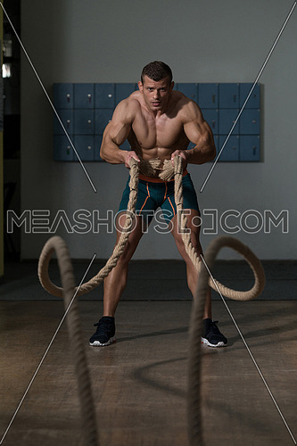 Battling Ropes Young Man At Gym Workout Exercise