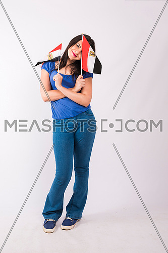 Young lady standing and holding two small egyptian flags on white background.