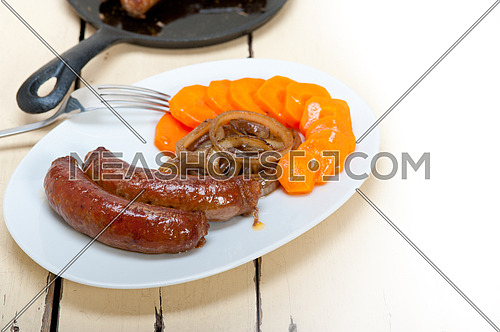 beef sausages cooked on iron skillet with carrot and onion