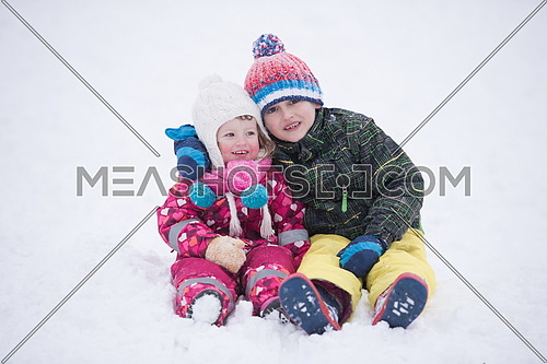 group of children having fun and play together in fresh snow on winter vacation