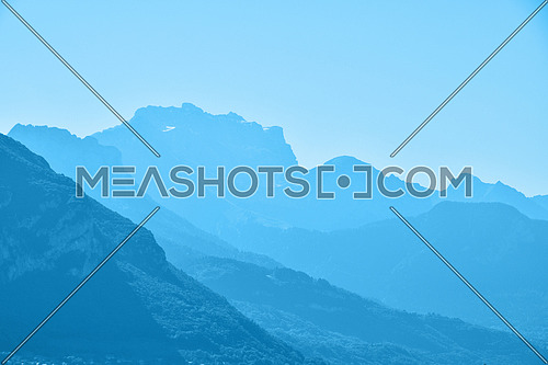 Blue toned aerial perspective mountain range landscape with clear sky copy space