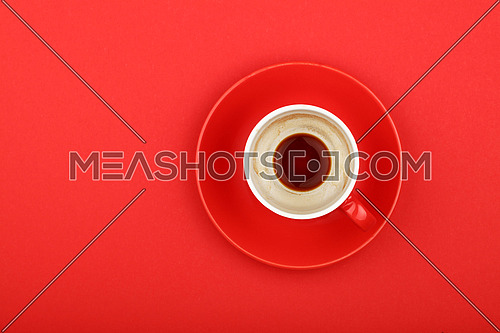 One empty finished morning espresso coffee shot in small red cup with saucer on red paper background, top view, bird eye view