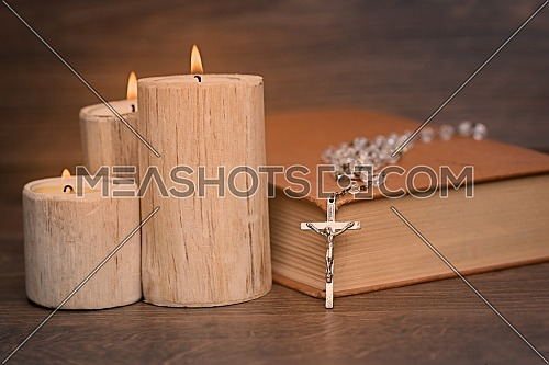 Silver rosary and crucifix resting on closed book near the candles on wooden table, religion school concept. Vintage style.